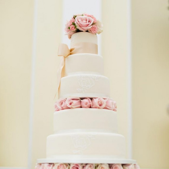 Pink roses decorating the wedding cake in the Orangery at Blenheim Palace, Oxfordshire