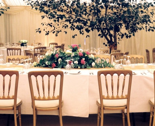 Elegant beautiful long & low table piece in a tree filled Marquee Oxfordshire, Joanna Carter Wedding Flowers, Oxford, Buckinghamshire, Berkshire, Surrey London